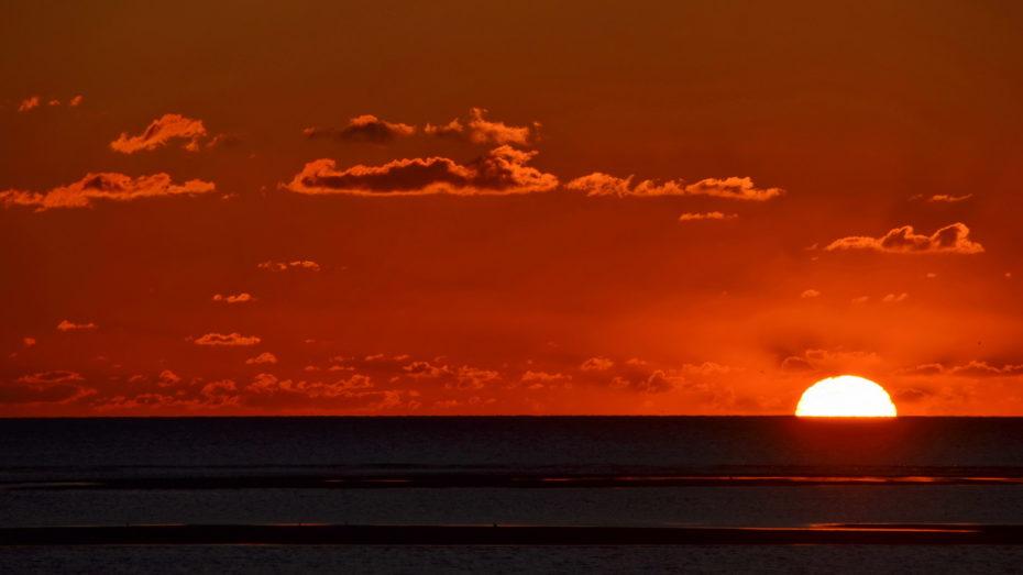 Sonnenuntergang am Meer halbe Sonne rot wenig Wolken Sandbänke