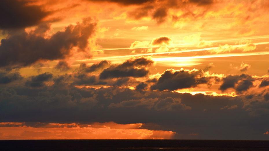 Sonnenuntergang hinter Wolken orange Gold Gelb große viele Wolken dunkel