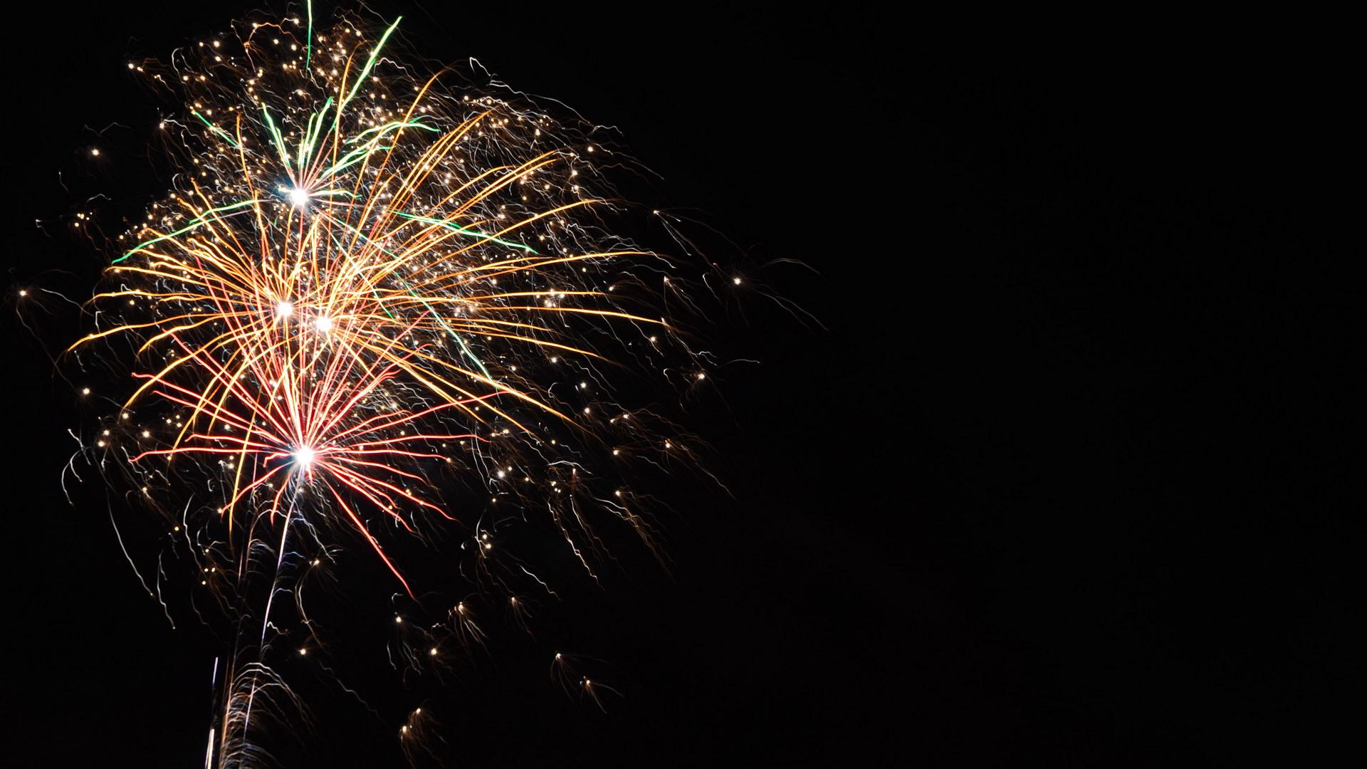 Silvesterfeuerwerk schwarzer Himmel Rakete Rot Grün Gelb Weiß