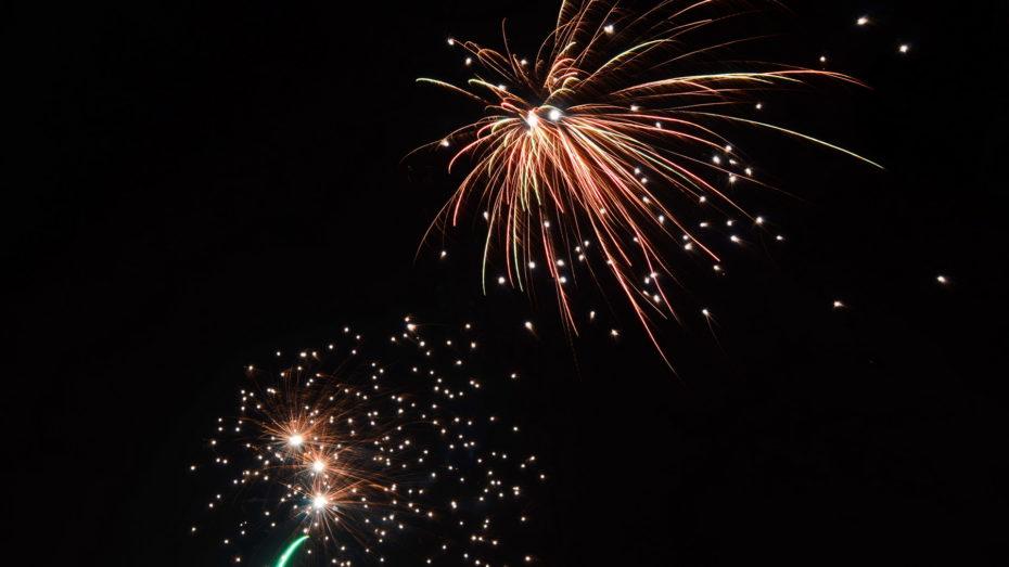 Feuerwerk schwarzer Himmel zwei Raketen Grün Rot Weiß