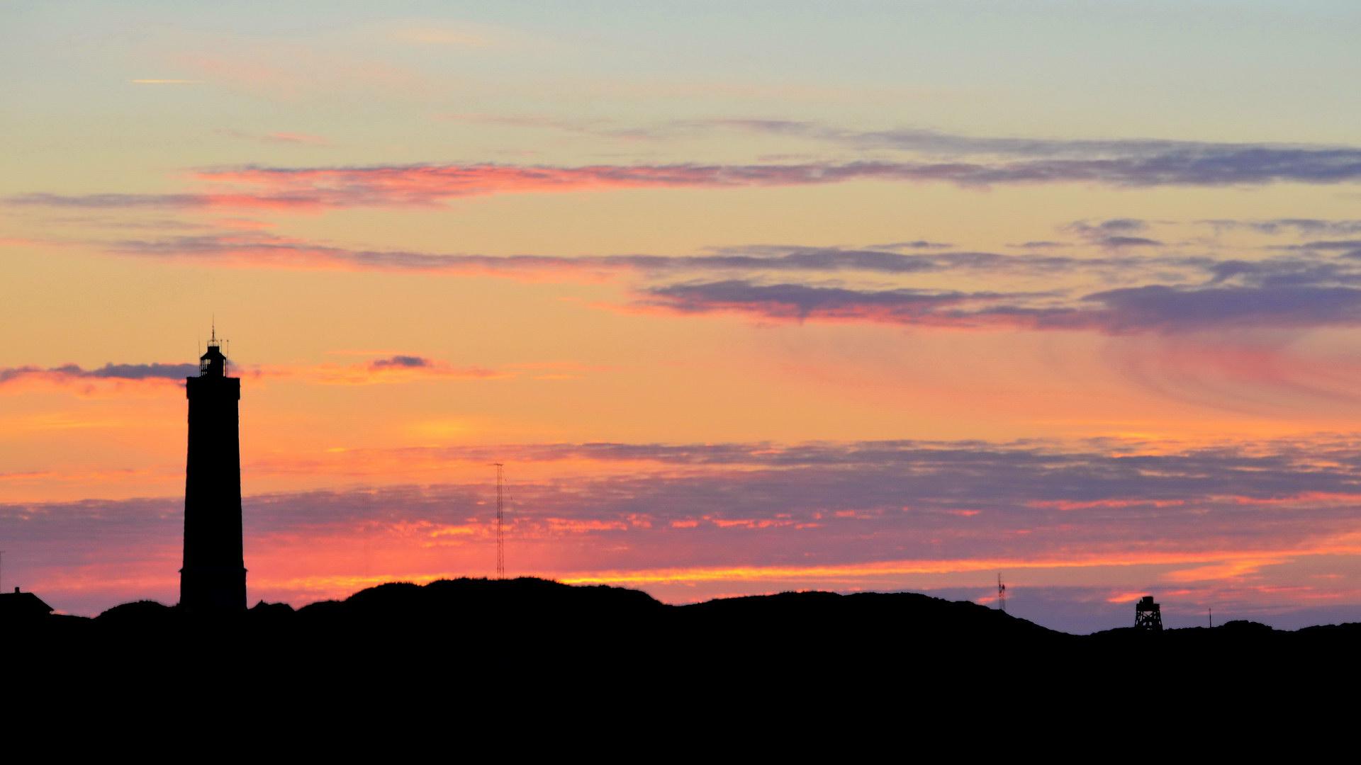 Leuchtturm vorm Sonnenuntergang Silhouette Landfläche Wolken Rot Blau