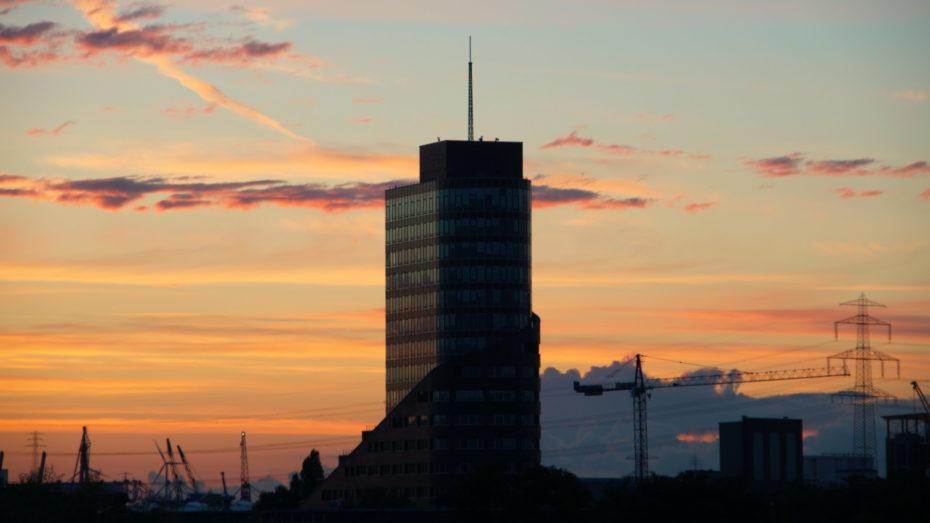 Channel Tower Hamburg Harburg Hochhaus vor Sonnenuntergang in der Stadt Kräne im Hintergrund Stromleitungen und Strommasten
