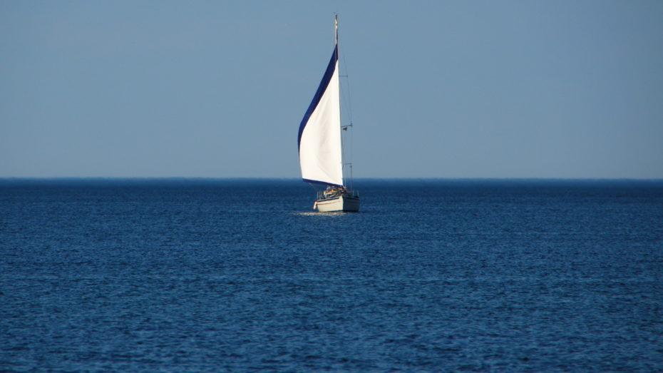 Segelschiff auf dem Meer Nur Wasser zu sehen und mittig das Segelboot. Weißes Segel mit blauem Rand
