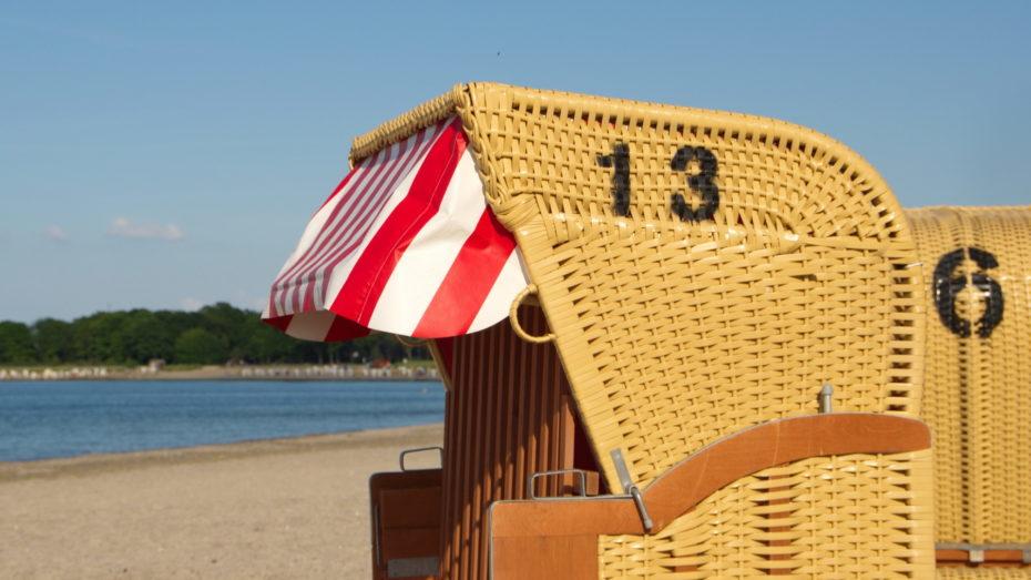 Strandkorb am Meer in der Sonne Nummer 13 drauf Rot Weißes Sonnendach Verschlossen 6 im Hintergrund und das Meer ist zu sehen