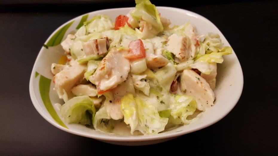 Salat Hähnchenfleisch Kräuter Gewürze Eisbergsalat Dressing Paprika in einer kleinen Schale